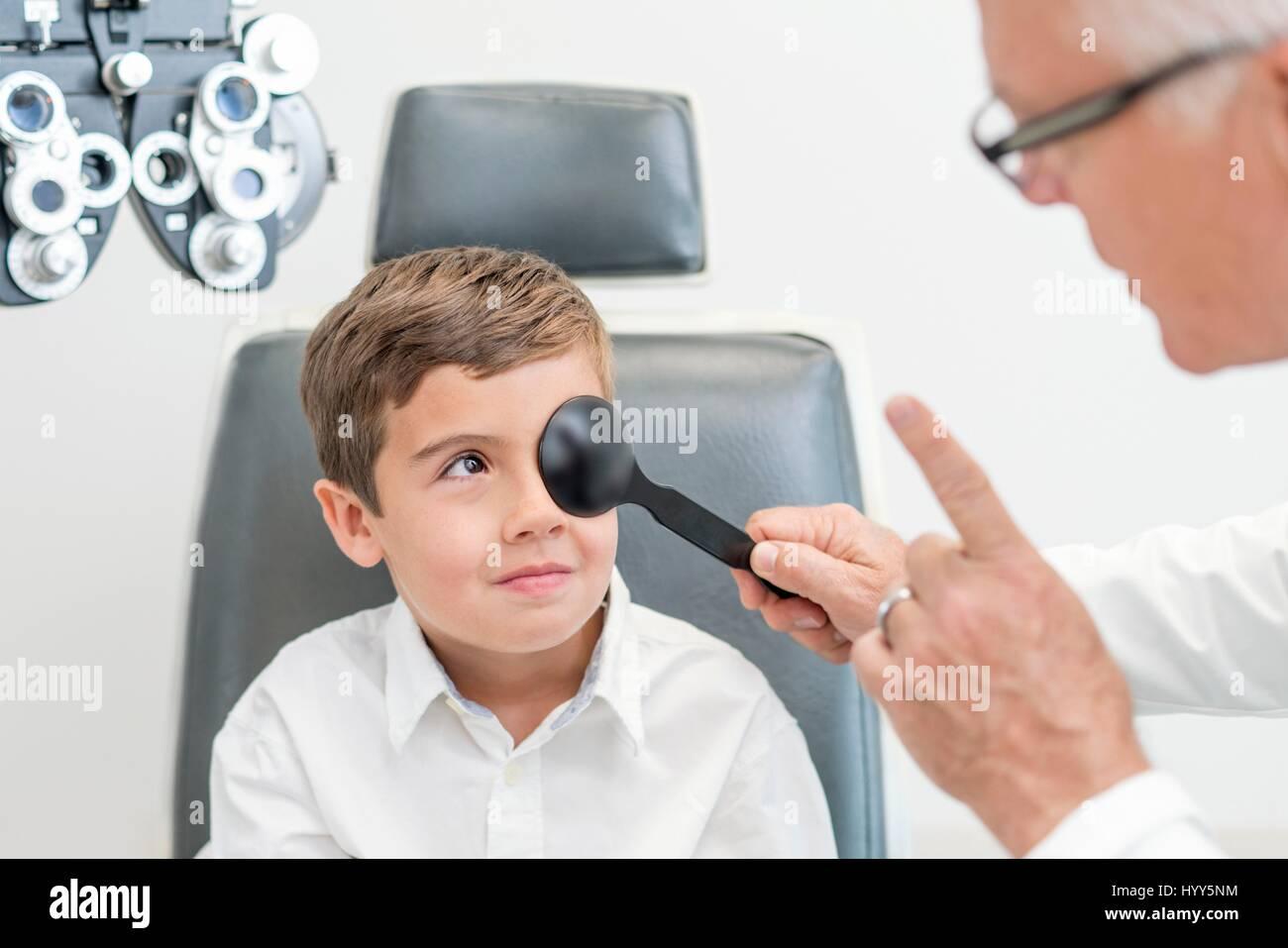 Male optician testing boy's eyesight. - Stock Image