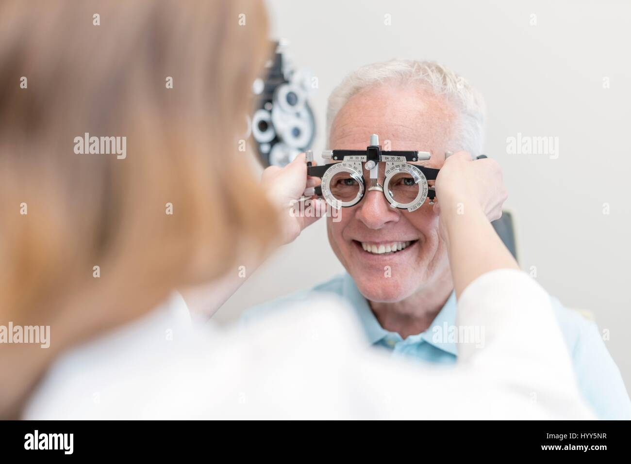 Optician testing man's eyesight. - Stock Image