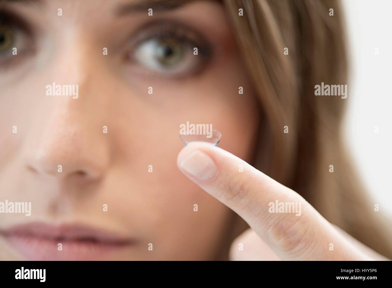 Mid adult woman with contact lens on finger. - Stock Image
