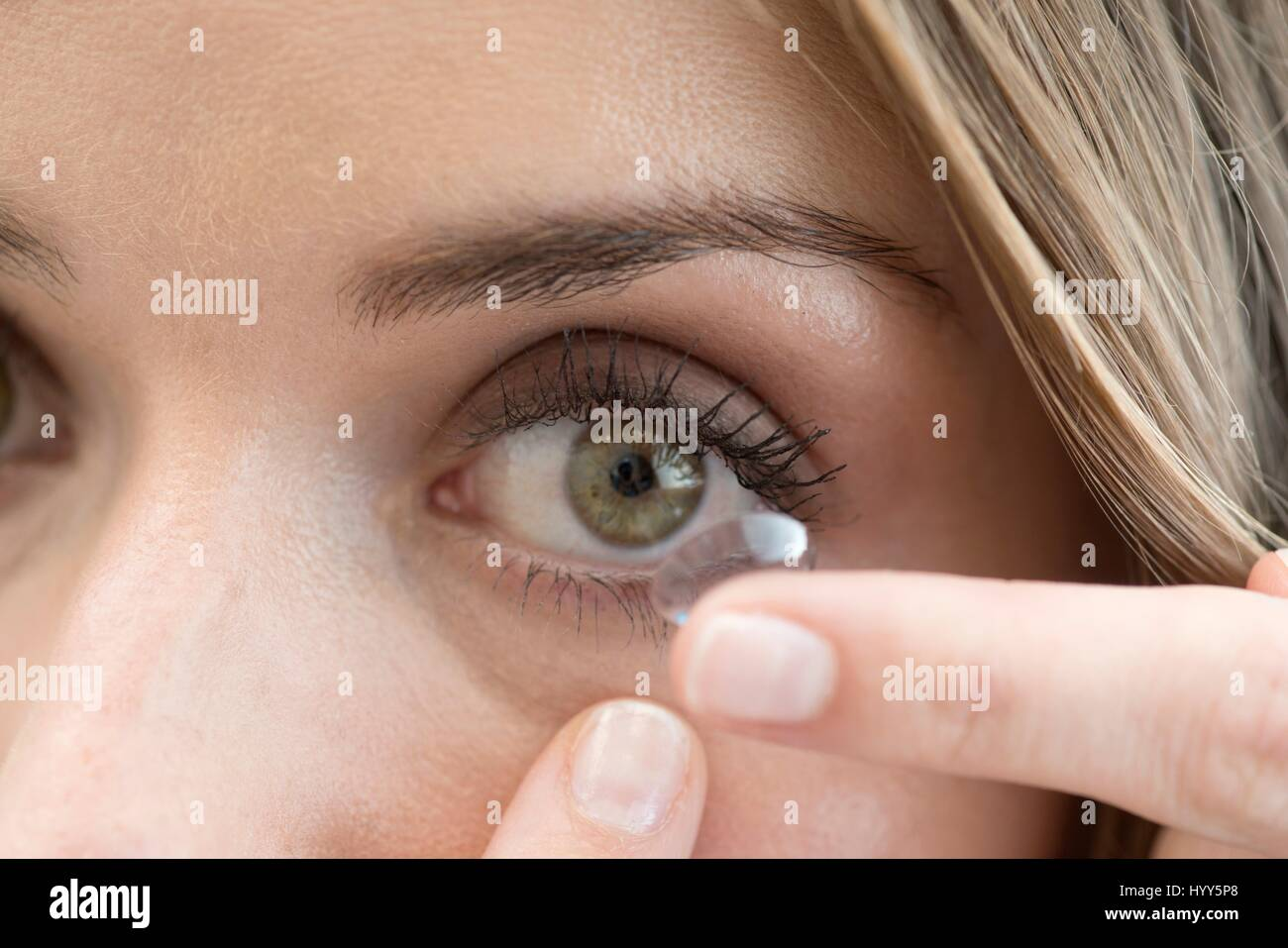 Mid adult woman putting contact lens in eye. - Stock Image