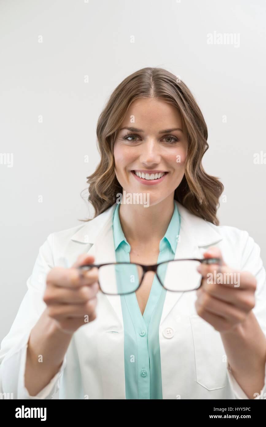 Female optician holding glasses. - Stock Image