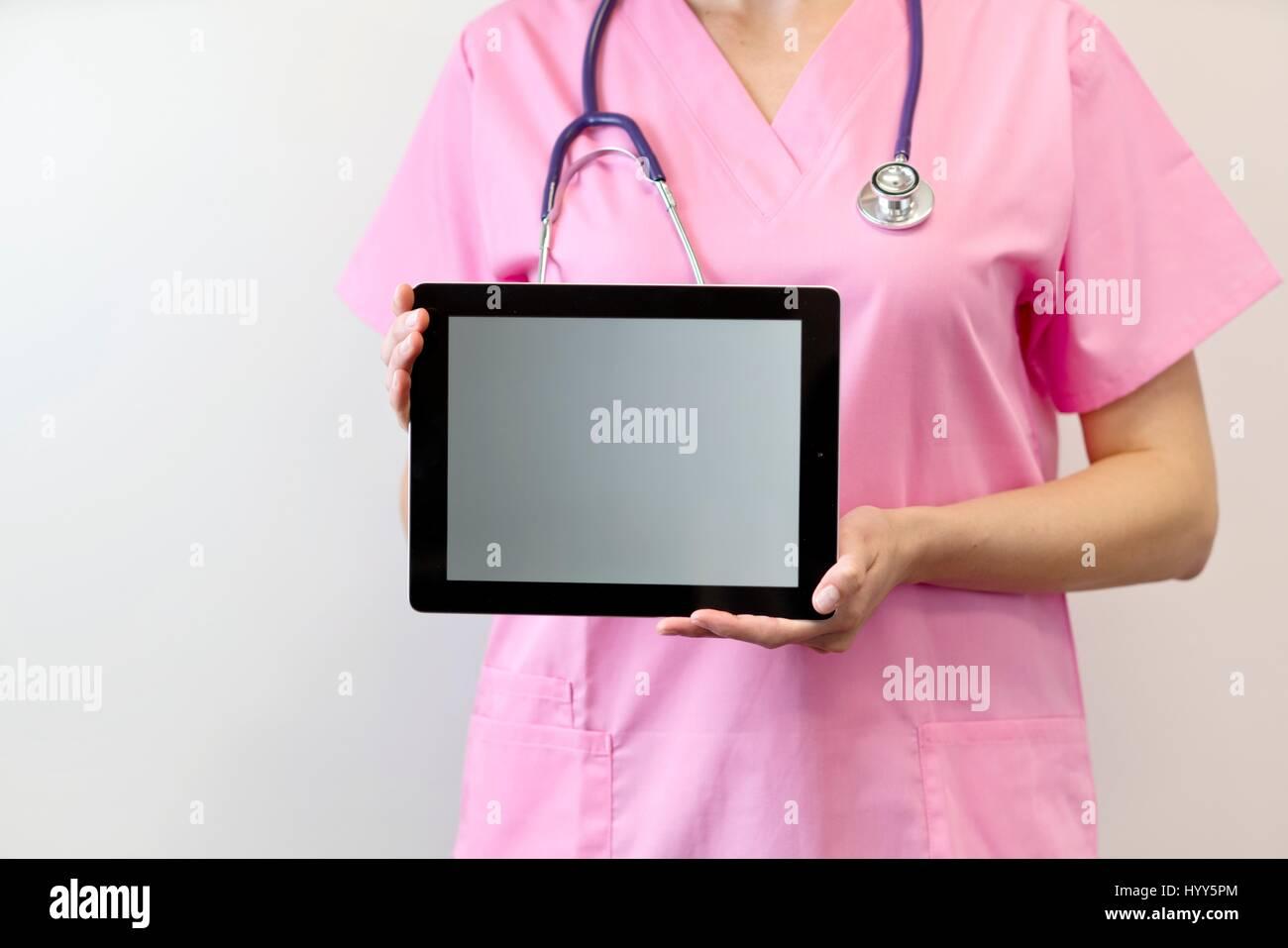 Female nurse holding digital tablet. - Stock Image