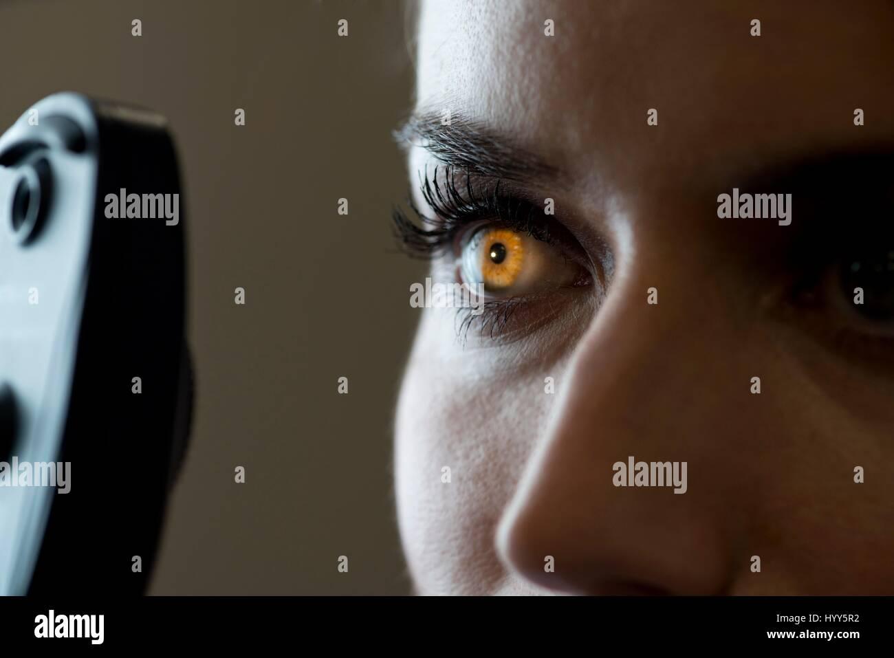 Woman having eye test with light shining in iris. - Stock Image