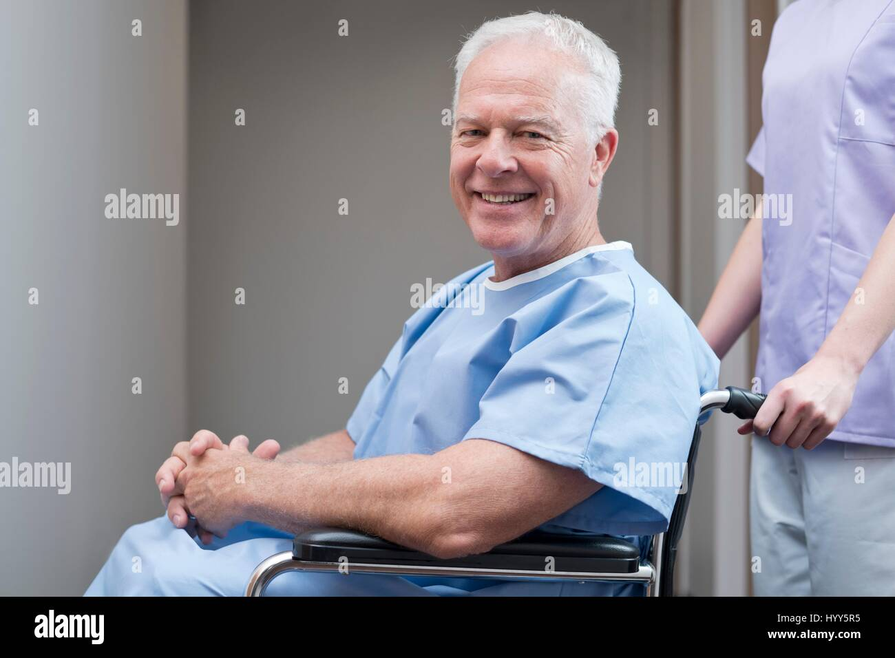 Senior man in hospital gown in wheelchair, smiling Stock Photo ...