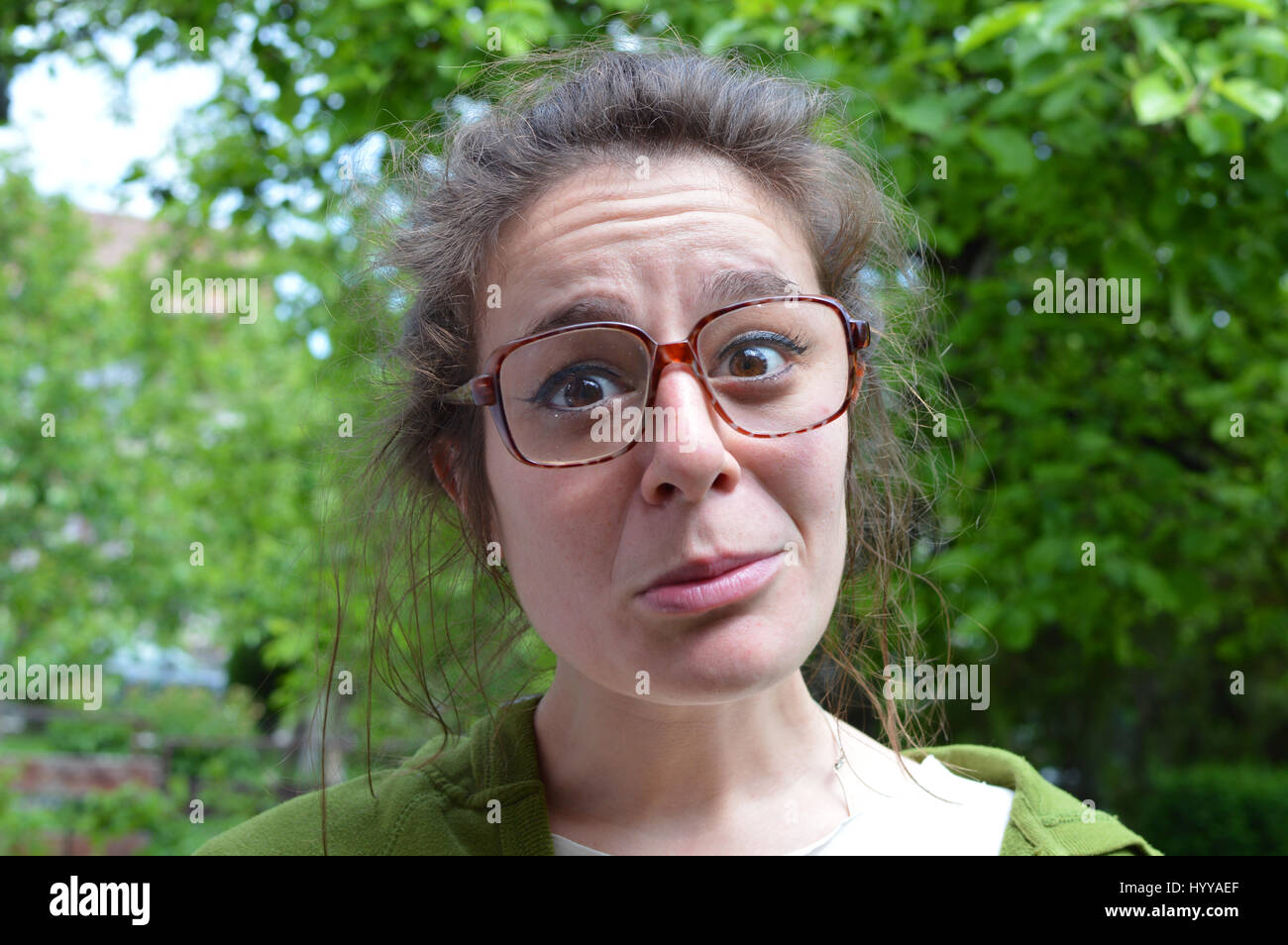Portrait of young nerd woman with big dioptric dusty glasses - Stock Image