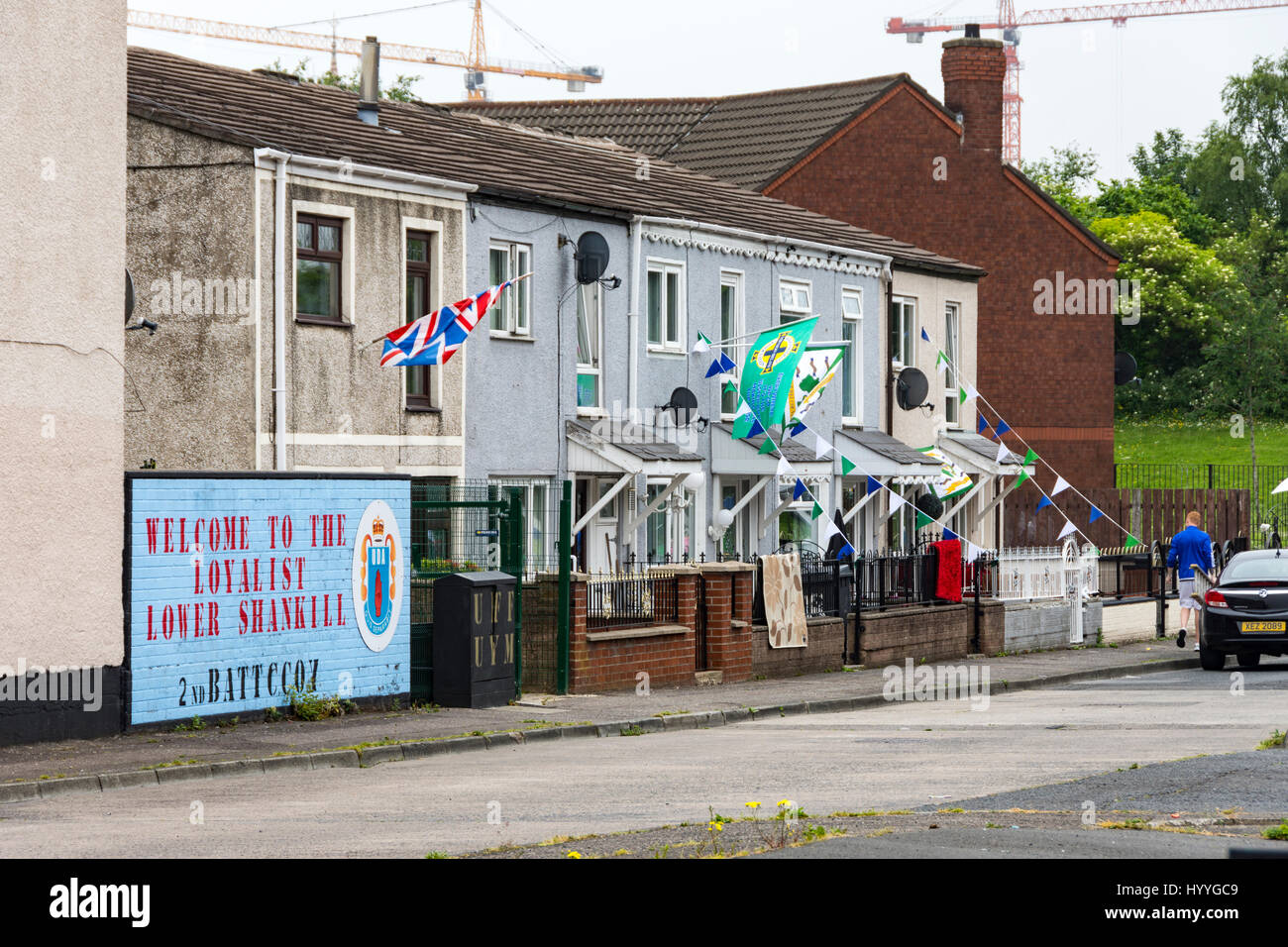 Houses with Loyalist mural and flags, Shankill estate, Belfast, County Antrim, Northern Ireland, UK - Stock Image