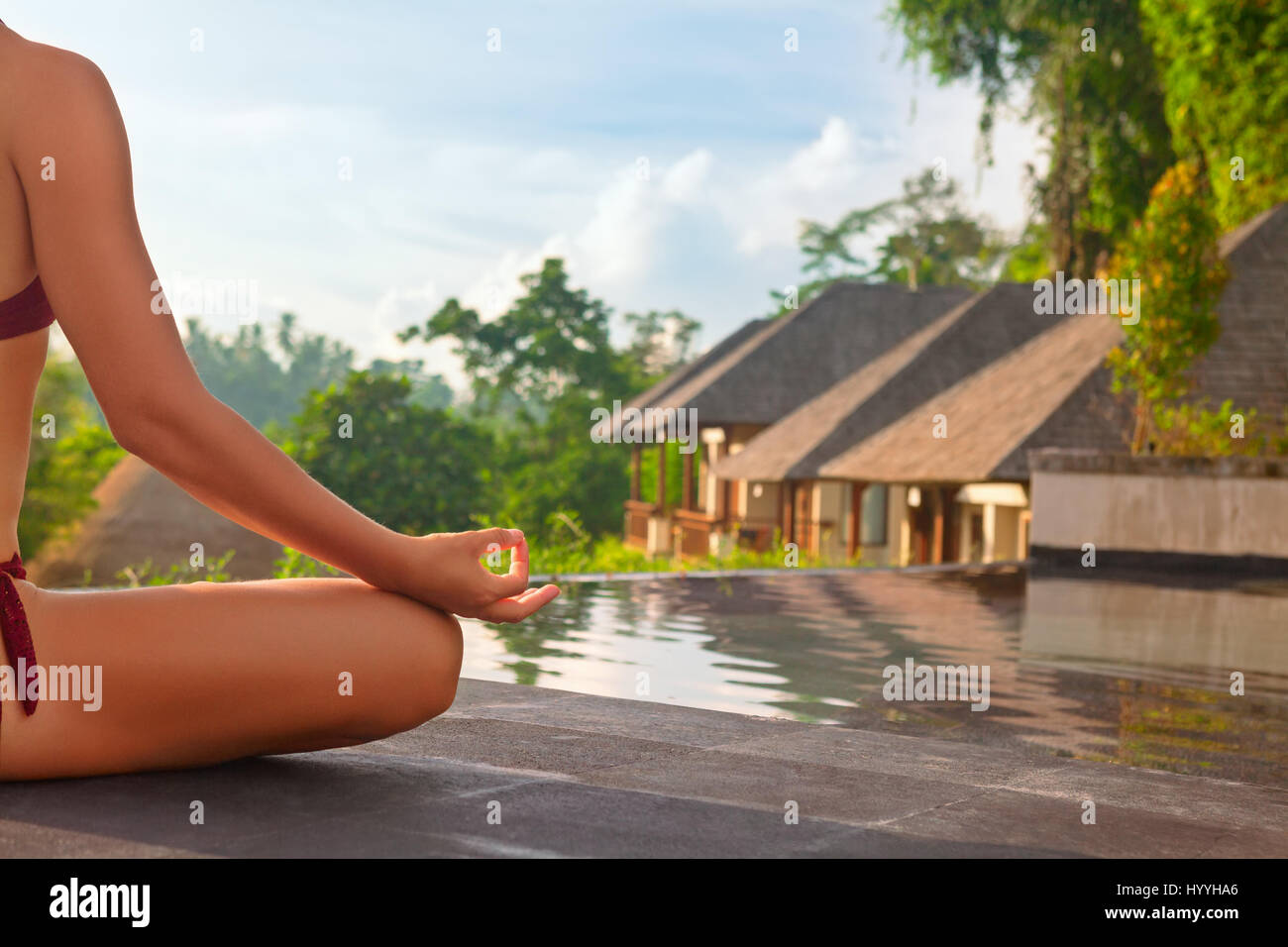Good morning with yoga meditating on sunrise background. Active woman in bikini practicing on villa poolside to Stock Photo