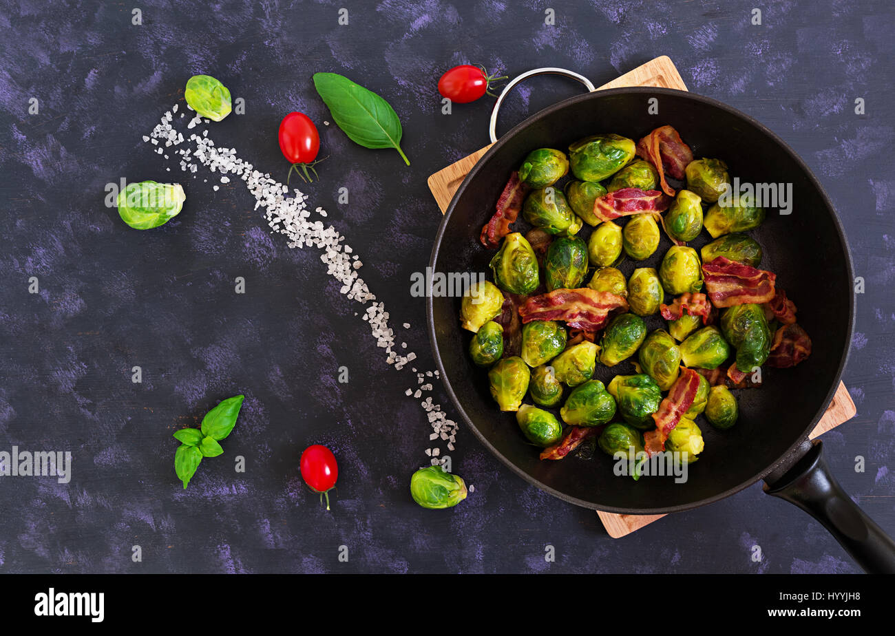 Roasted brussels sprouts with bacon on dark background. Top view Stock Photo