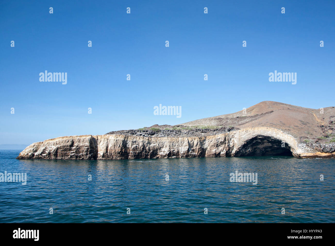 Sea cave eroded into tuff cliff (compacted volcanic ash) on Isabela Island in the Galapagos - Stock Image