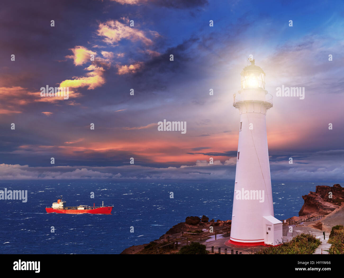 Sunset seascape, lighthouse on the bluff - Stock Image