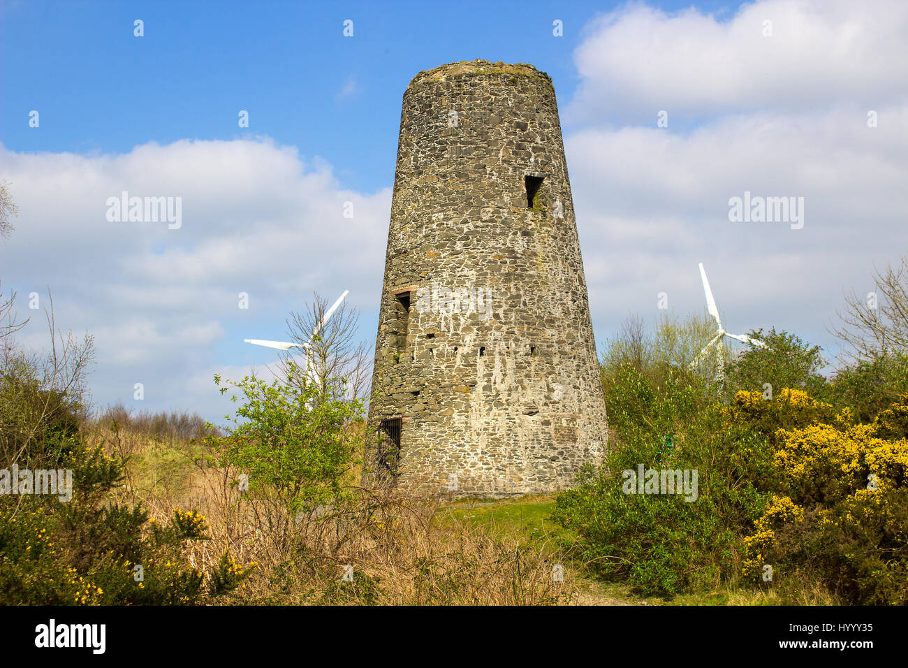 An old windmill stump in a 19th century lead mines with modern wind turbine vanes in the background in Conlig Northern - Stock Image