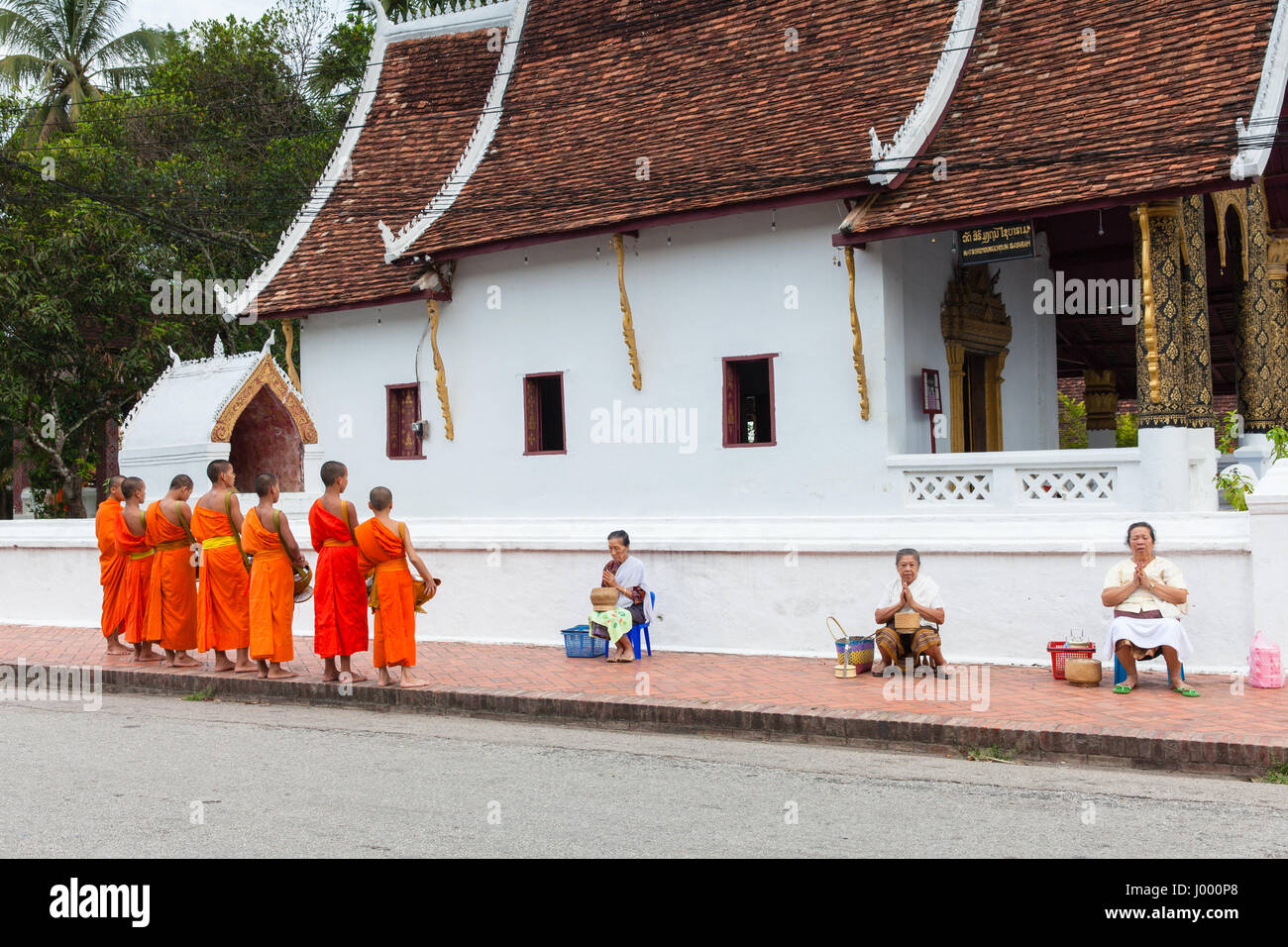 Lao People's Democratic Republic, Laos, Luang Prabang - 22 JUNE 2014: Woman prays after giving alms to buddhist Stock Photo