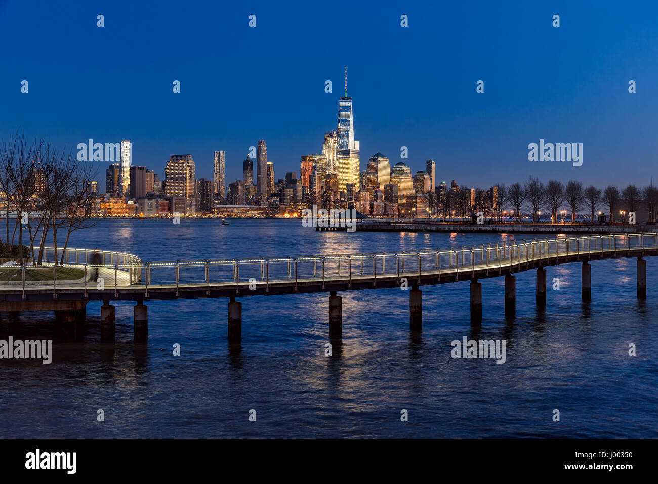 New York City Financial District skyscrapers at sunset and Hudson River from Hoboken promenade. Lower Manhattan - Stock Image