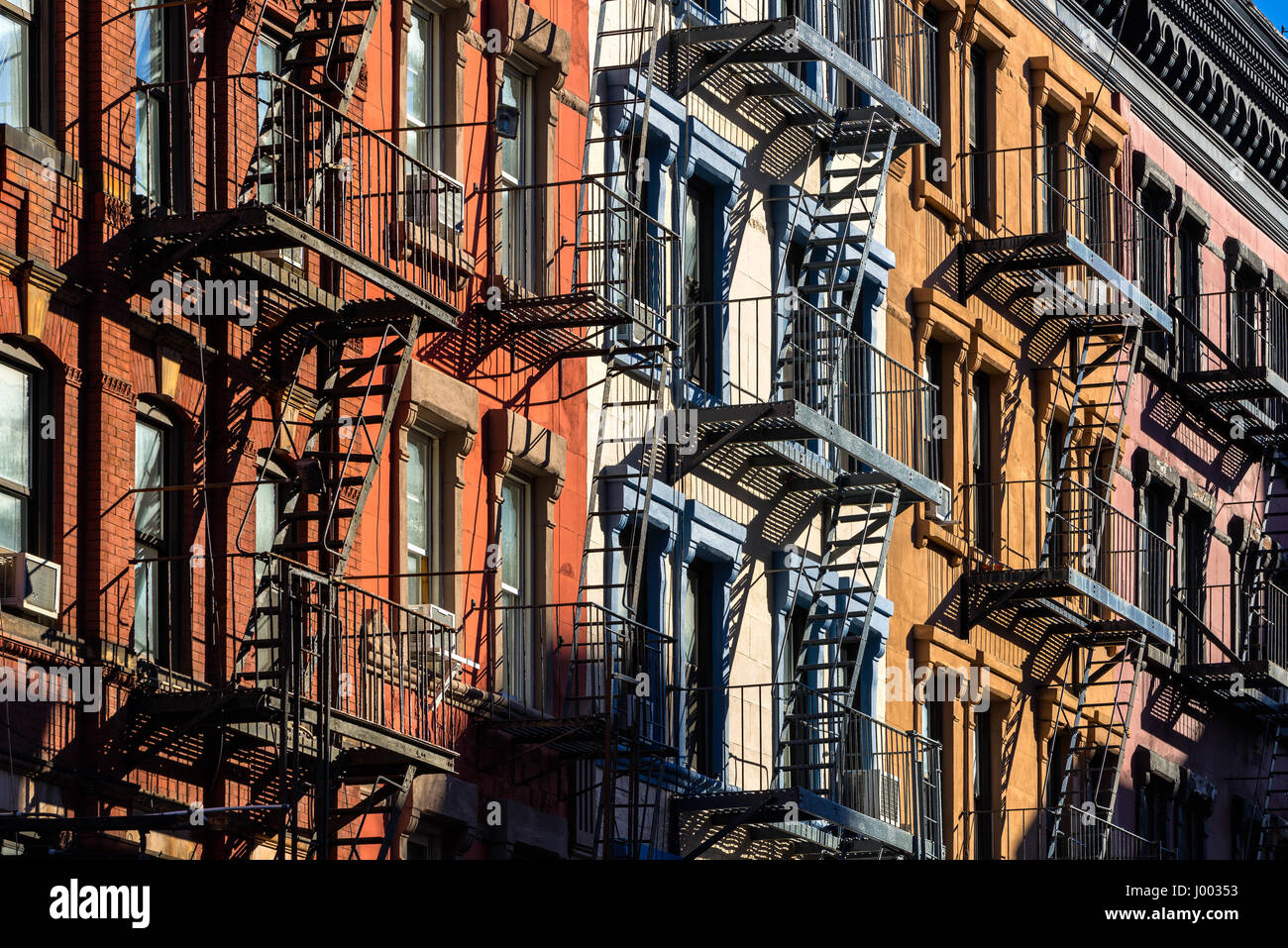 Colorful Soho building facades with painted fire escapes. Manhattan, New York City - Stock Image