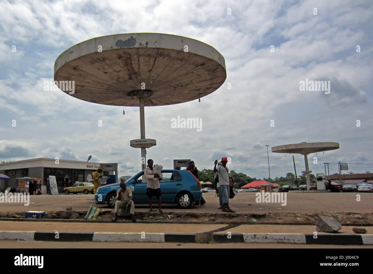 Blue car and some people in front of an old petrol station waiting for refuel, next to a road in the city of Lagos, - Stock Image