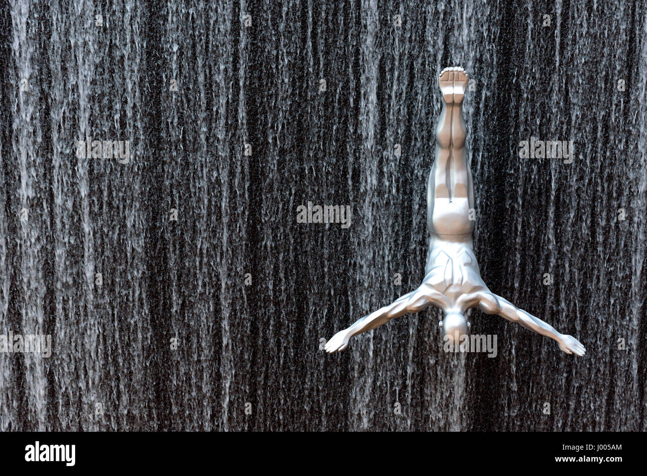 silver male sculpture installed to create a jumping effect on the fountain of Dubai Mall in Dubai, United Arab Emirates. - Stock Image