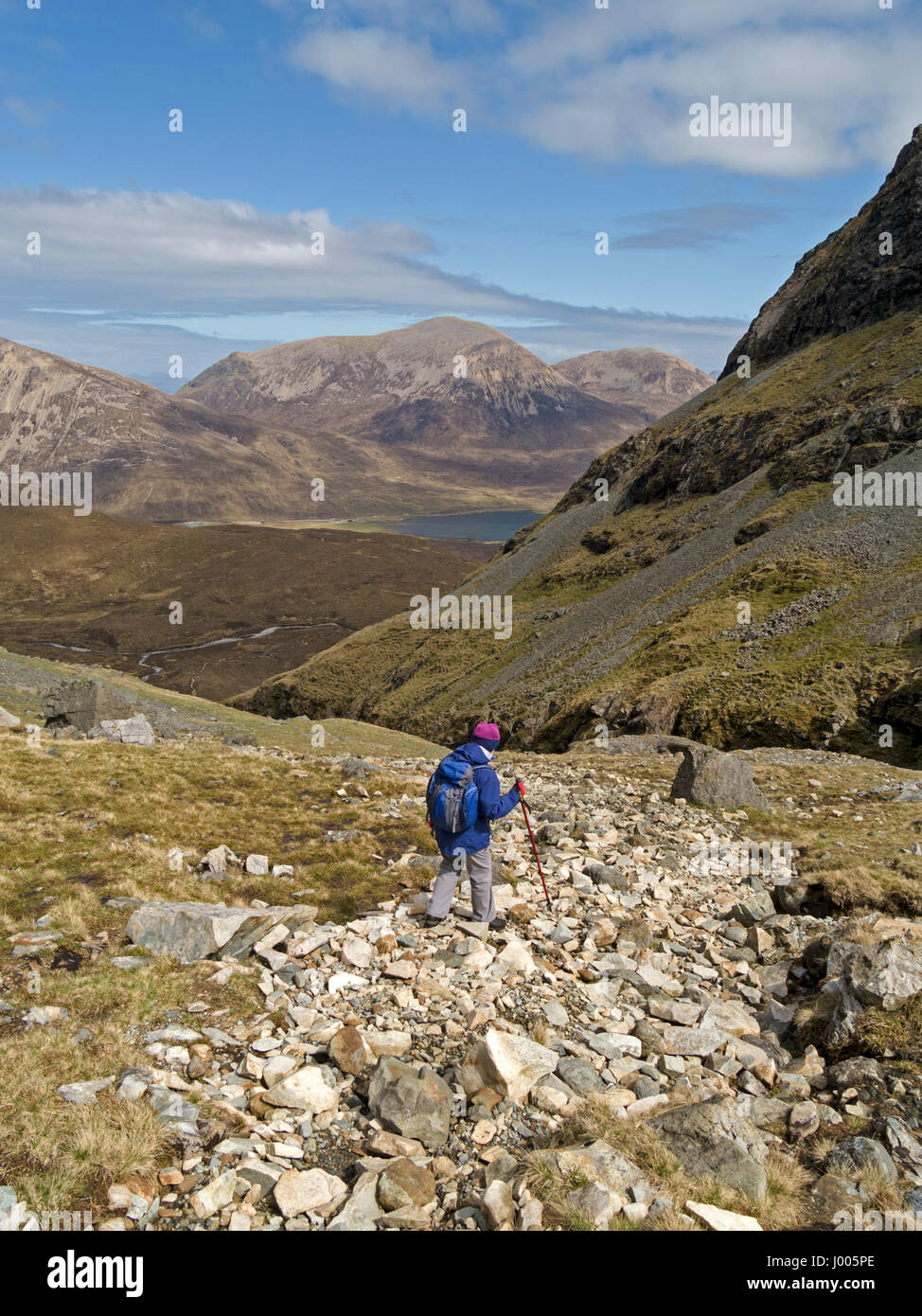 Female hill-walker descending from Blaven on the Isle of Skye with the Red Cuillin mountains in the distance, Scotland, - Stock Image