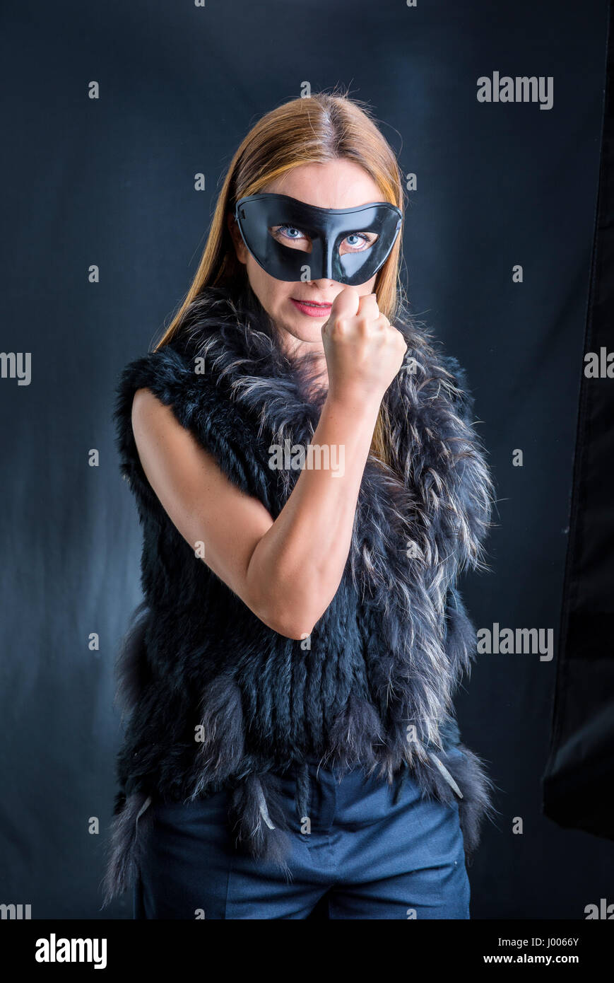 Woman in black mask performing - Stock Image