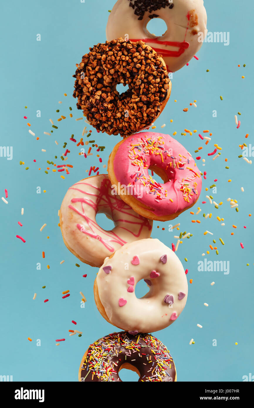 Various decorated doughnuts in motion falling on blue background. Sweet and colourful doughnuts falling or flying - Stock Image