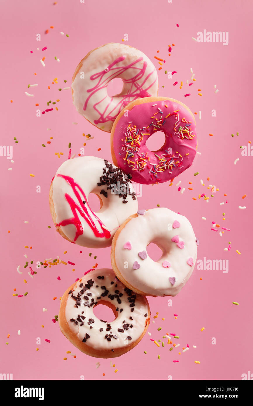 Various Decorated Doughnuts In Motion Falling On Pink