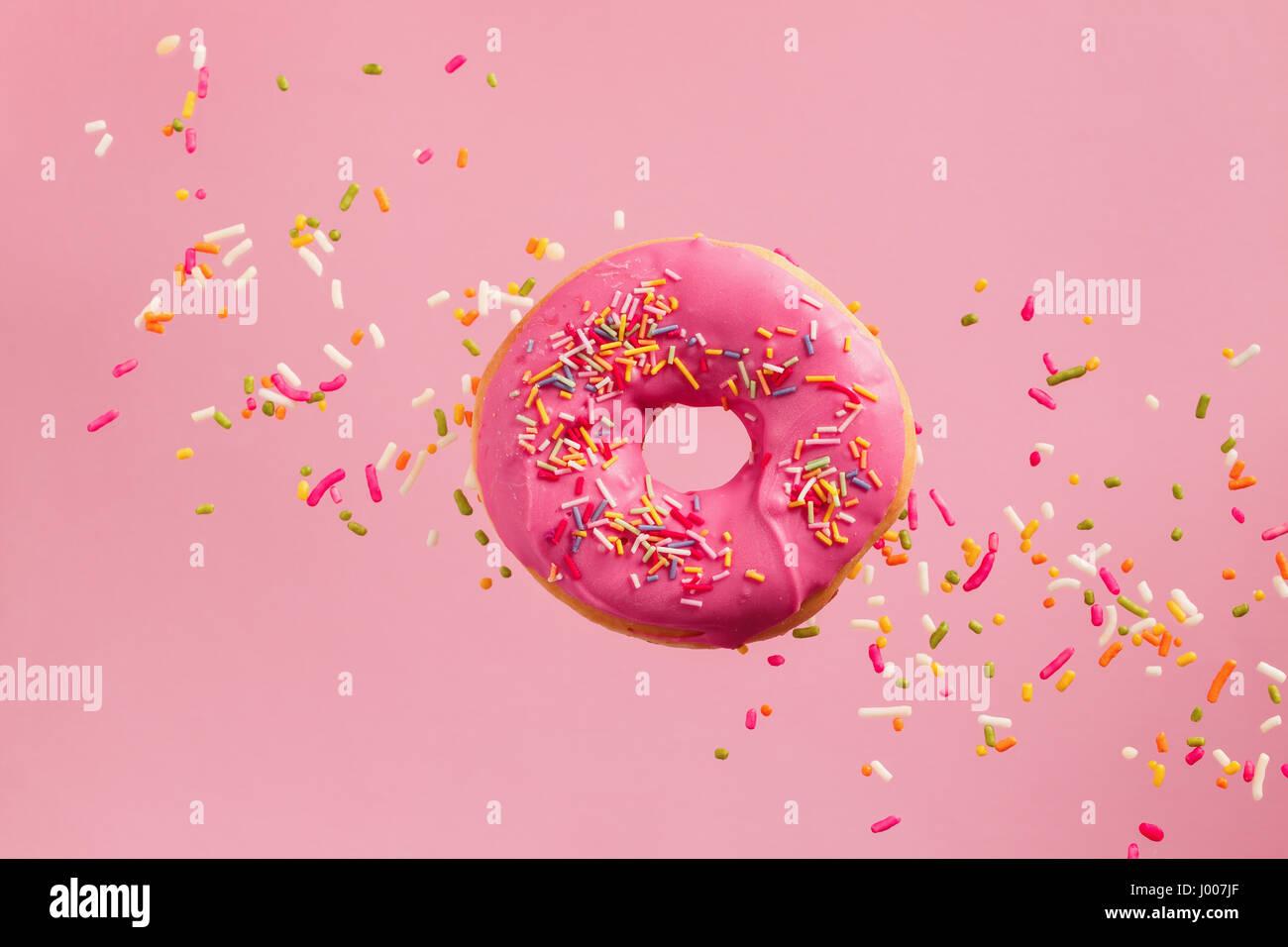 Sprinkled Pink Donut. Pink frosted sprinkled donut on pink background. - Stock Image