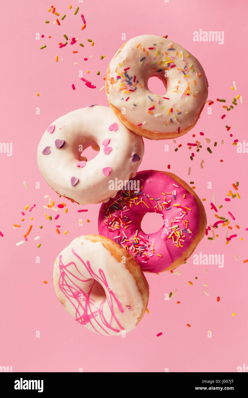 Various decorated doughnuts in motion falling on pink background. Sweet and colourful doughnuts falling or flying - Stock Image