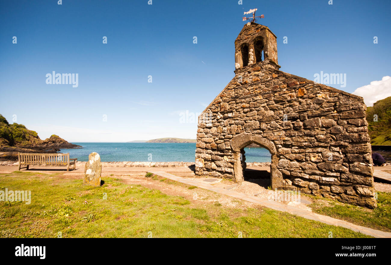 The ruined gable end wall of the chapel beside the sea at Newport Bay and Dinas Island in the Pembrokeshire Coast - Stock Image