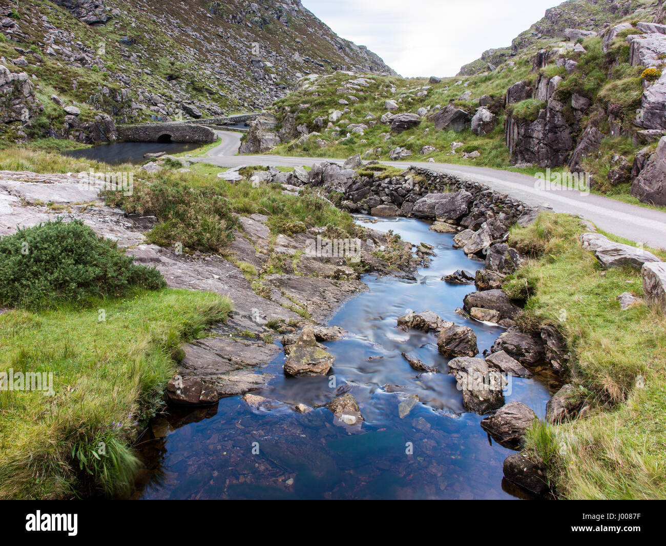 The River Loe & narrow mountain road wind through the Gap of Dunloe valley, nestled in the Macgillycuddy's Reeks Stock Photo