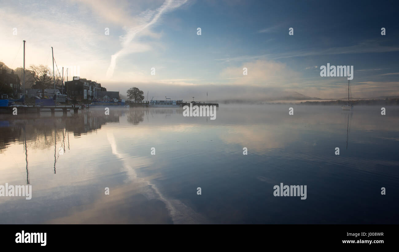 Mist rises from the calm waters of Windermere lake at Waterhead Pier, beside Ambleside Youth Hostel, in England's - Stock Image