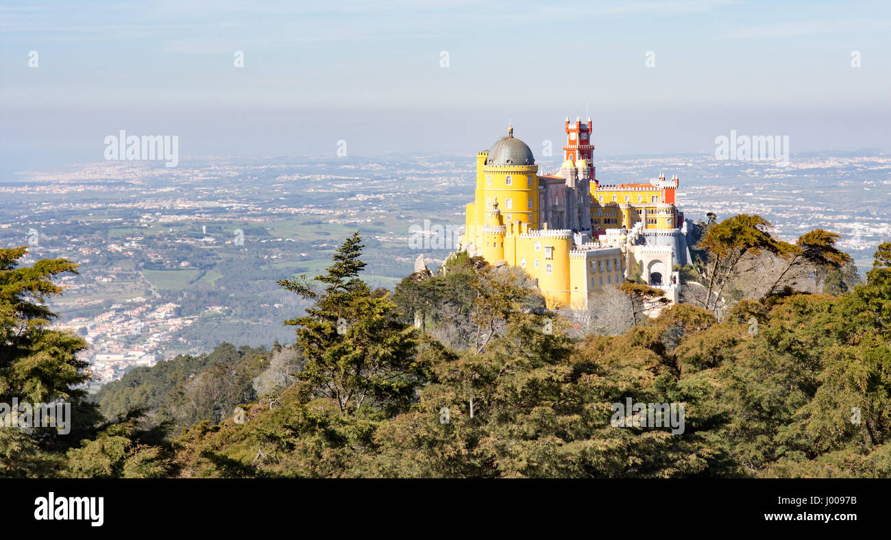 The cliche view of the fairytale Palacio da Pena royal palace from the High Cross on the mountaintop at Sintra near - Stock Image