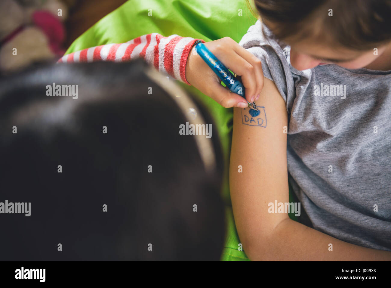 Girl Writing Tattoo On Arm Of Her Girlfriend With Pen Stock Photo