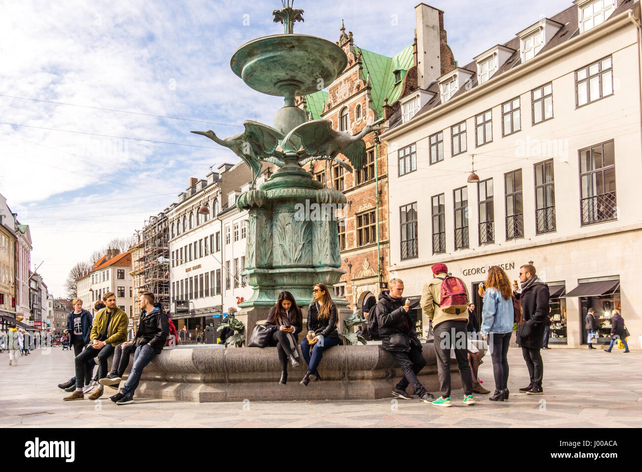 The Stork Fountain with young people sitting on the edge. Amagertorv in central Copenhagen, Denmark - Mars 23, 2017 - Stock Image