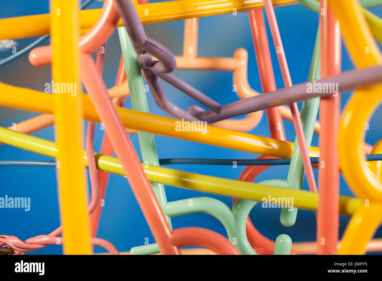 Macro detail of a jumble of colorful clothes hangers - Stock Image