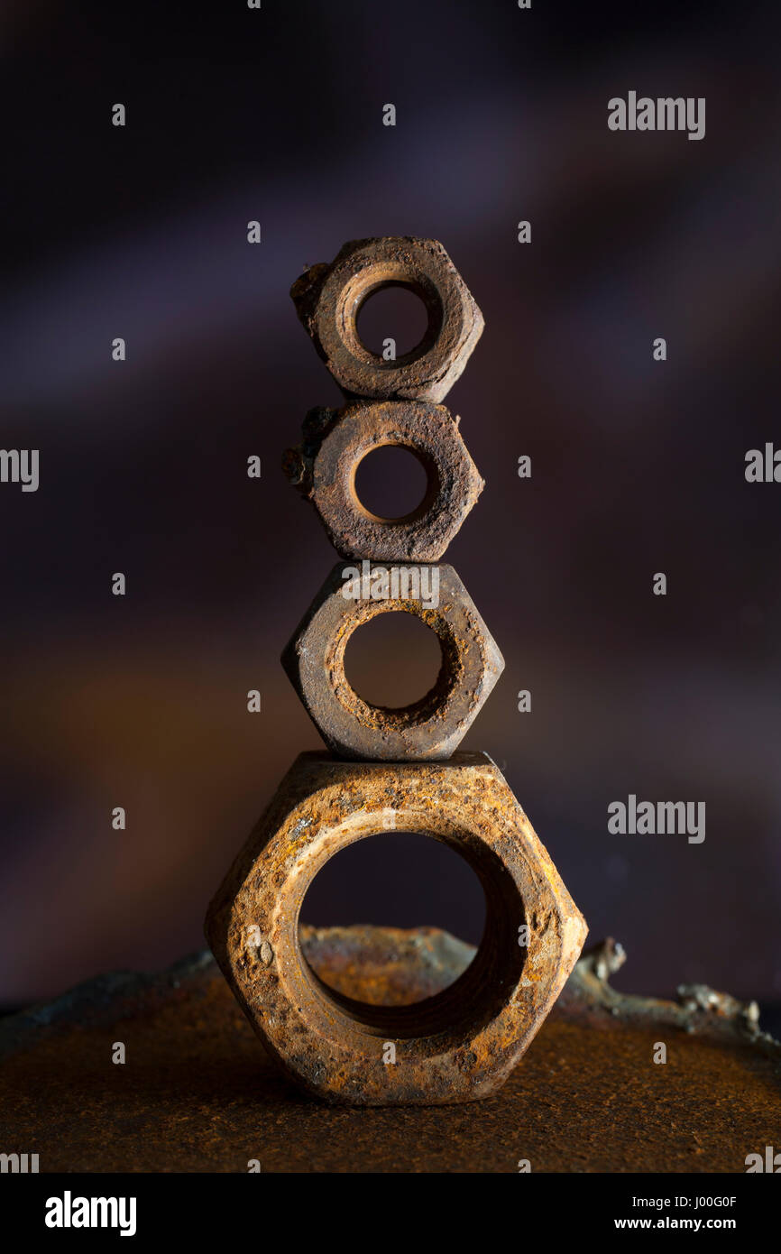 Macro composition of rusty old nuts balanced on top of eachother Stock Photo