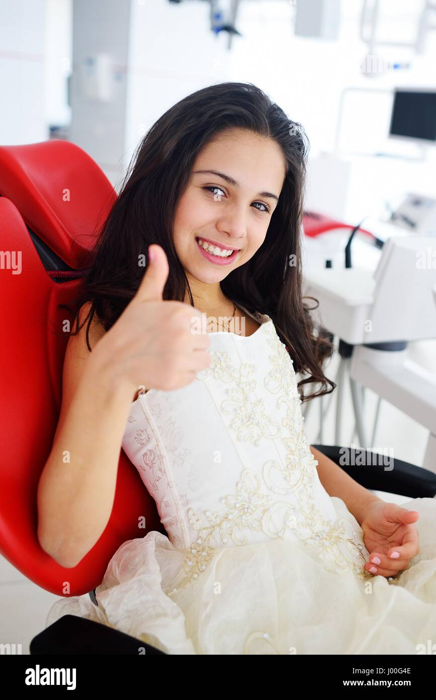 Baby cute girl in a smart dress in a red dental chair shows a thumb up - Stock Image