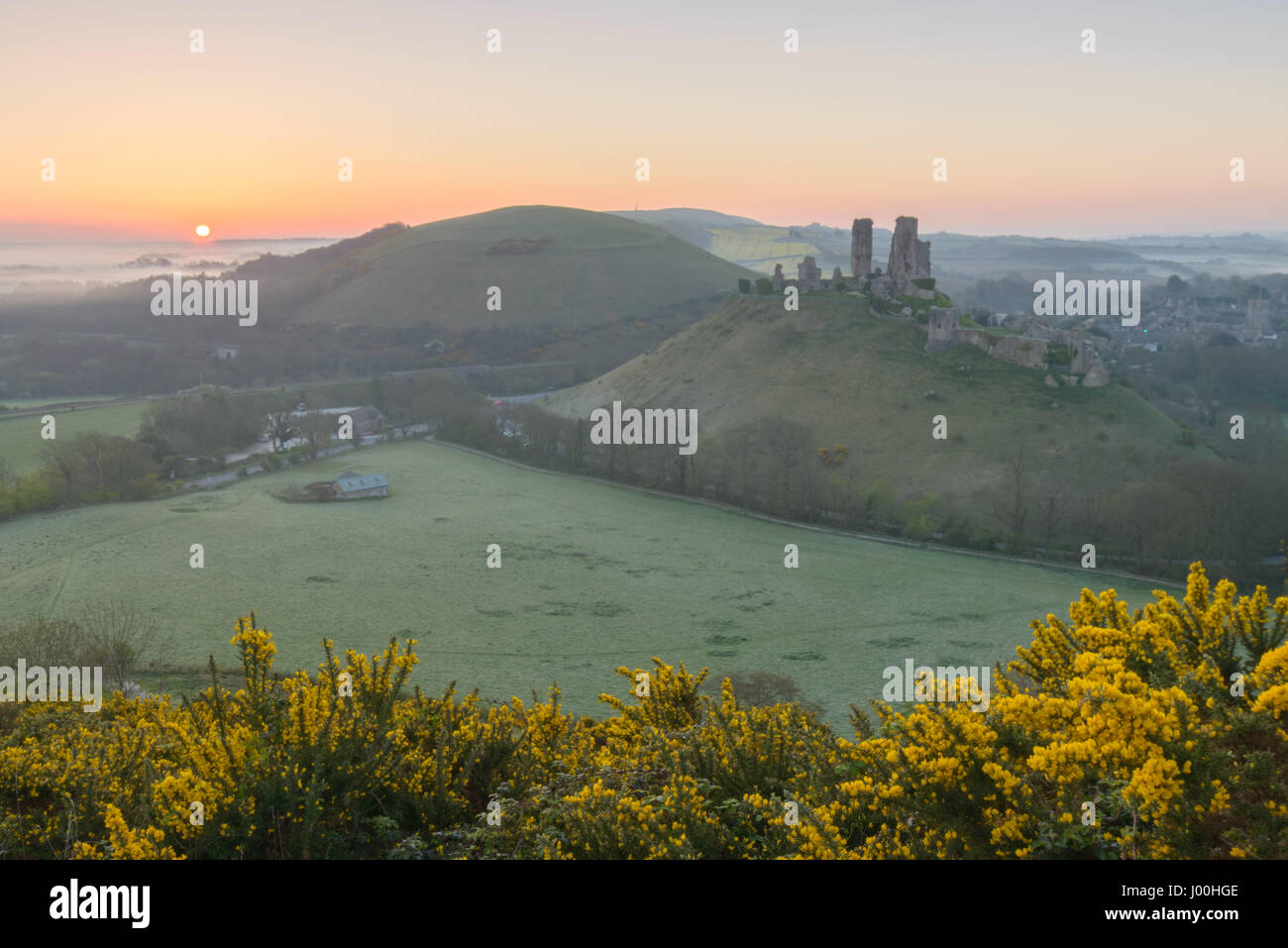 Corfe Castle, Dorset, UK. 8th April 2017. Glorious misty crisp sunrise over the Isle of Purbeck and the iconic, - Stock Image