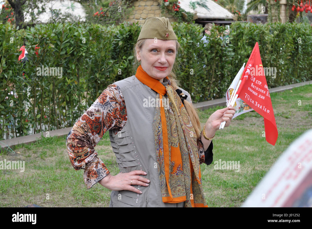 Woman selling communist flags during a Day of Spring and Labour. - Stock Image