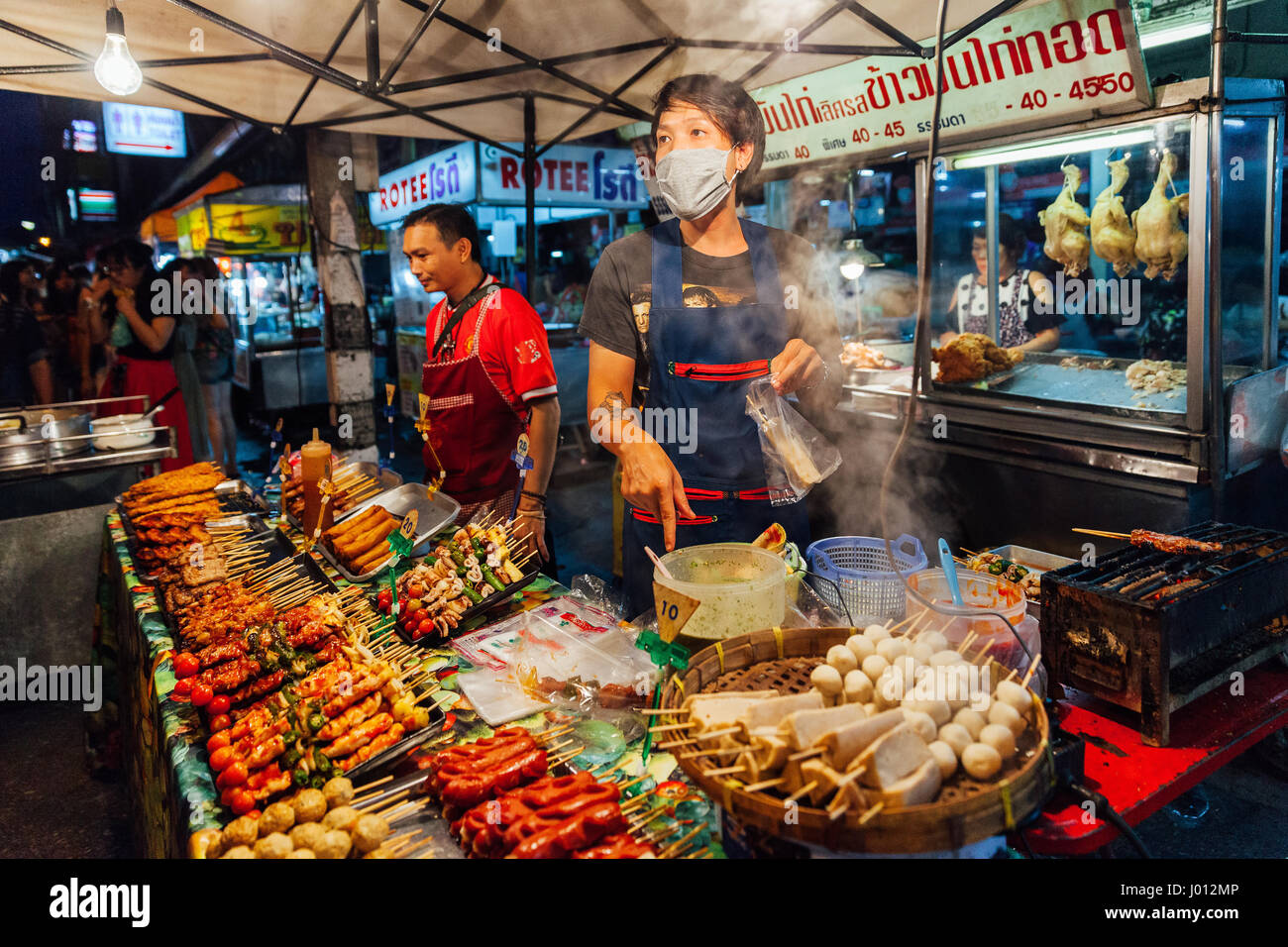 Chiang Mai, Thailand - August 27, 2016: Young men sell satay at the Saturday Night Market on August 27, 2016 in - Stock Image