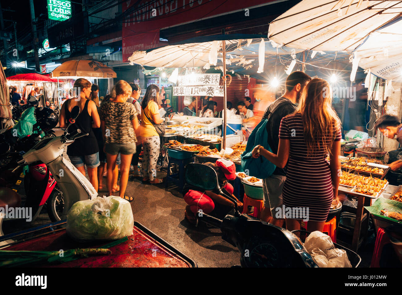 Chiang Mai, Thailand - August 27, 2016:  Tourists choose food at the Saturday Night Market on August 27, 2016 in - Stock Image