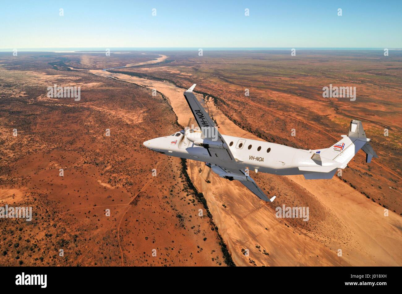 An aerial view of a Beechcraft B1900D short-haul / charter airliner banking over the Australian outback. - Stock Image