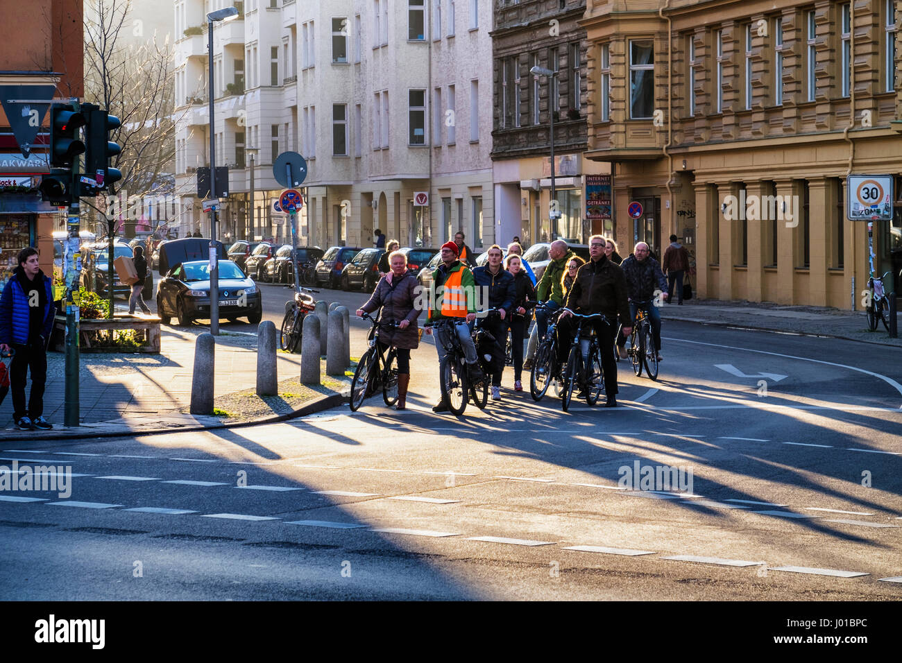 Berlin, Mitte. Group of middle aged tourists on bicycles exploring the City on bikes.Cyclists tour by cycling. - Stock Image