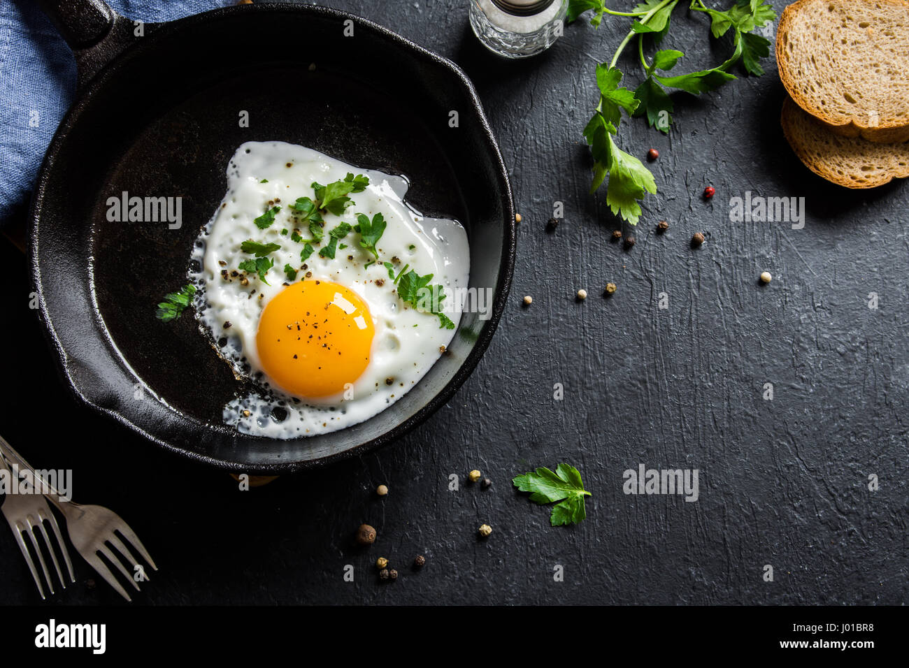 Fried egg. Close up view of the fried egg on a frying pan. Salted and spiced fried egg with parsley on cast iron - Stock Image