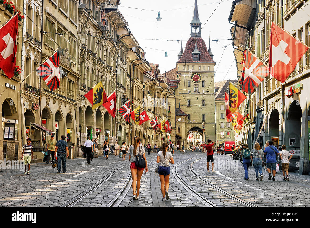 Bern, Switzerland - August 31, 2016: Girls and other people at Kafigturm tower on Marktgasse street with shopping - Stock Image