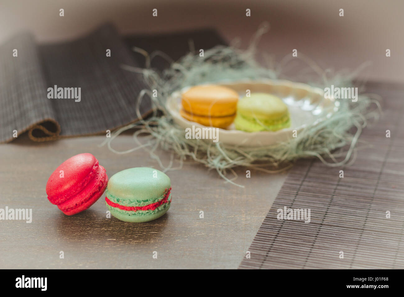 Traditional french macaroons, two on the table and two on the plate behind. Selective focus, vignette, pastel color - Stock Image