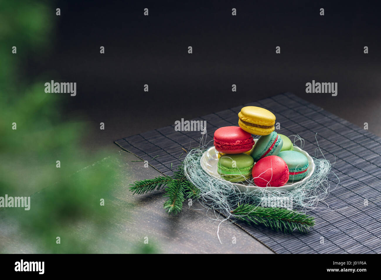 Winter still life with traditional French macaroons on the small plate and fir tree branches. Space for your text - Stock Image
