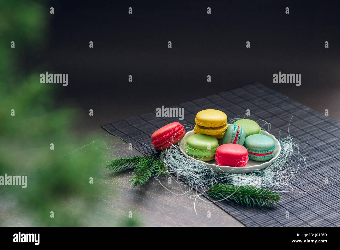 Winter still life with traditional French macaroons on the small plate and fir tree branches. Space for your text Stock Photo