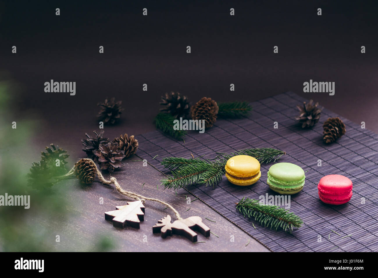 Three macaroons in a row on the table with fir tree branches, cones and Christmas ornaments - Stock Image