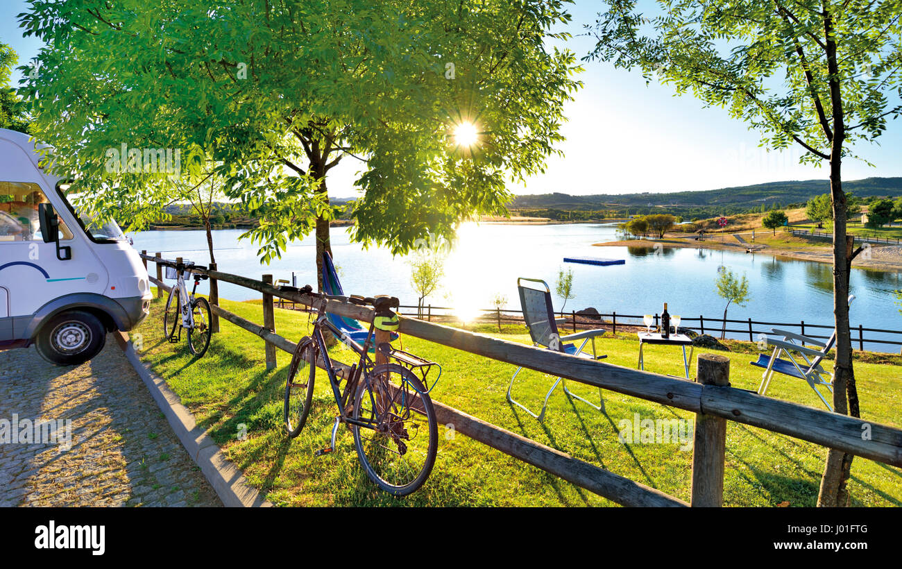 Motorhome and bike parking at romantic chill-out point  with camping chairs, table, wine and lake view - Stock Image