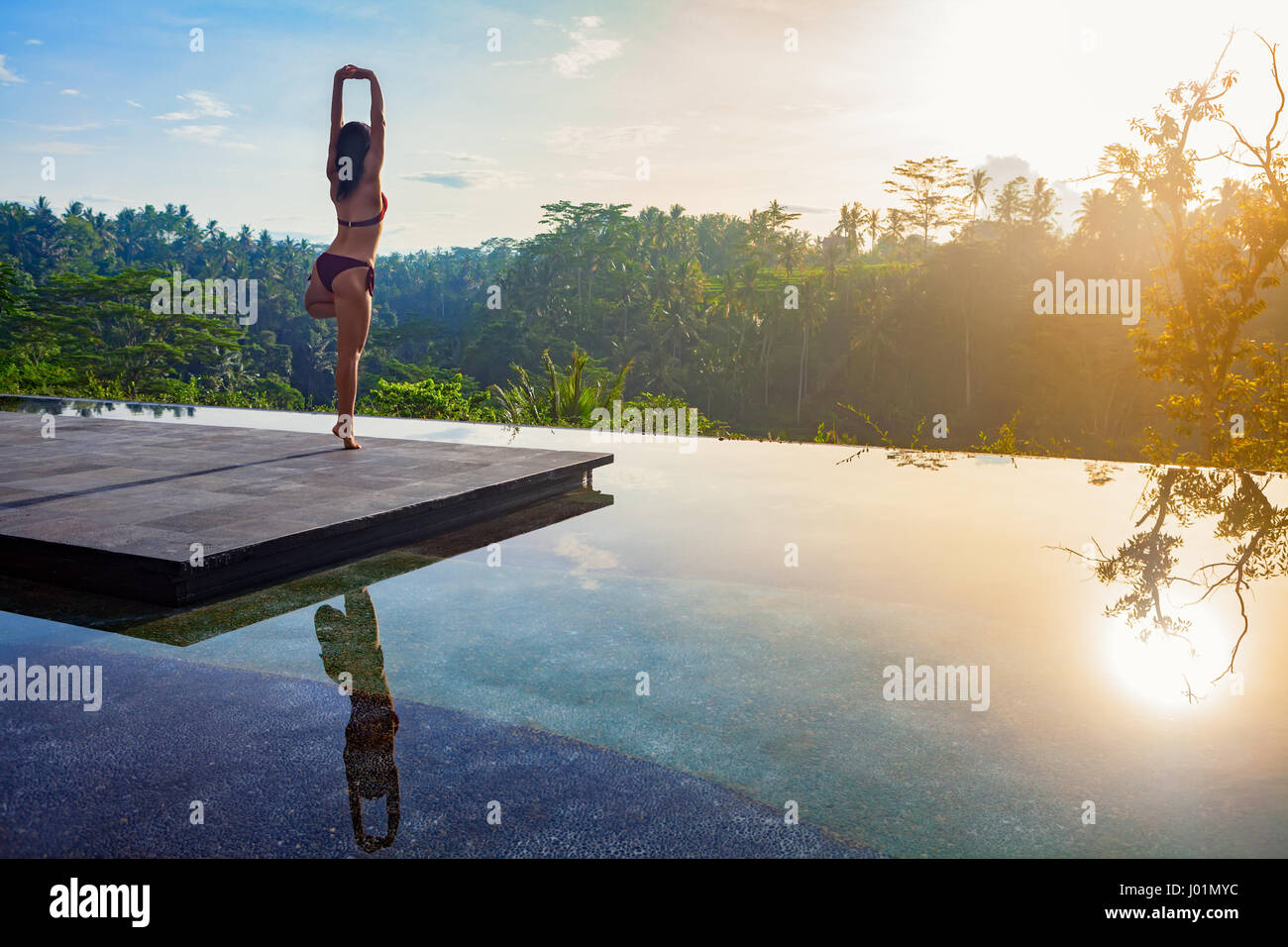 Good morning with yoga meditating on sunrise background. Active woman in bikini practicing on villa poolside to - Stock Image
