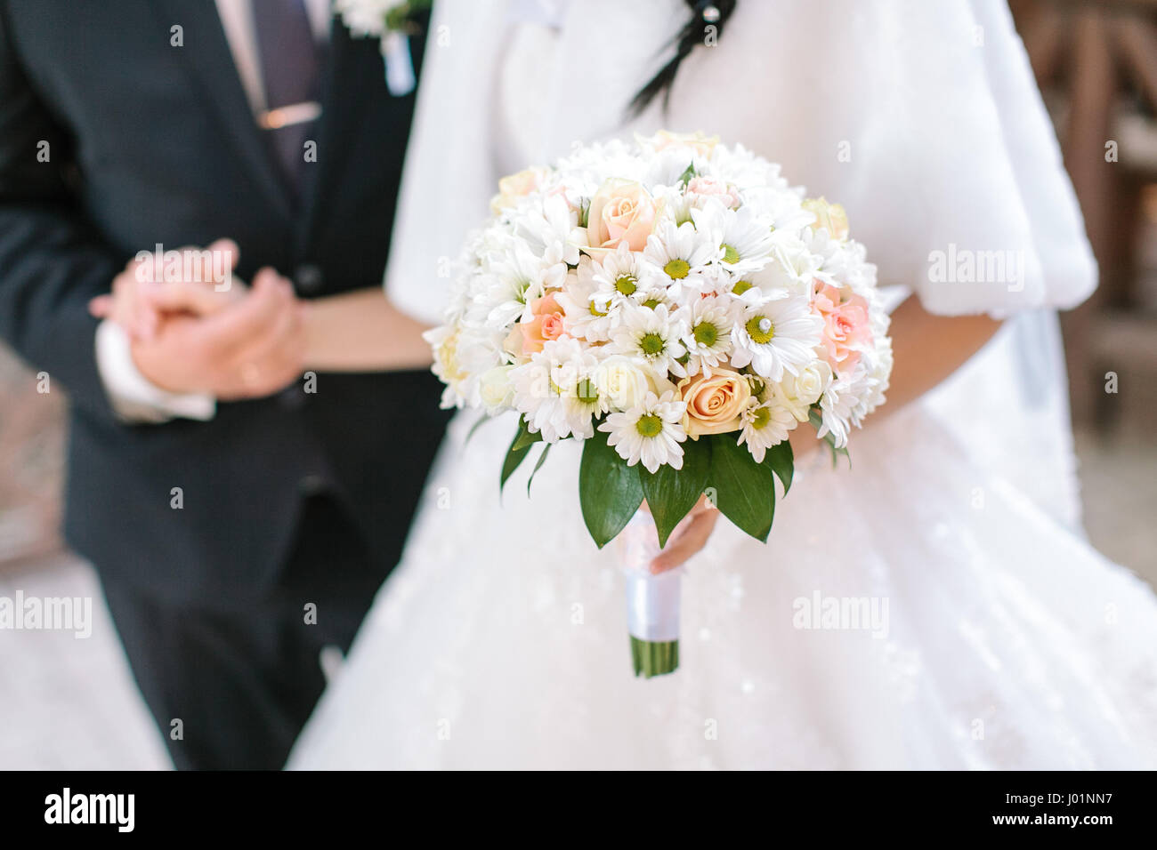 Wedding bouquet from fresh spring flowers bride holding white stock wedding bouquet from fresh spring flowers bride holding white wedding bouquet close up the groom holding by a hand the bride in a white wedding dres izmirmasajfo